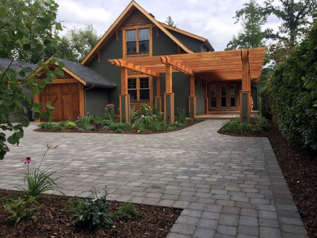 Custom brick driveway with pergola with large planting bed