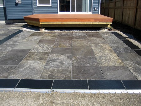 Natural stone patio with black boarder